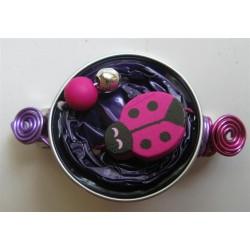 Barrette coccinelle fuchsia sur capsule violette