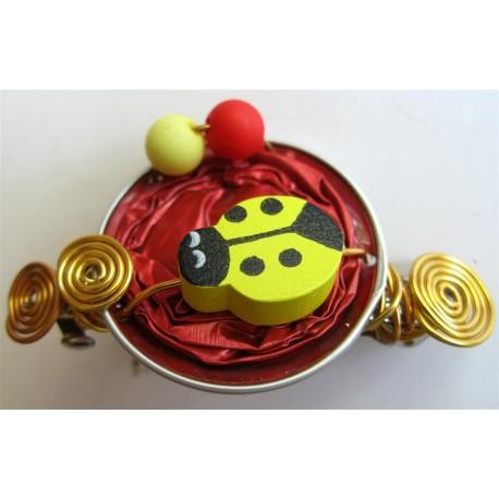 Barrette coccinelle jaune sur capsule rouge